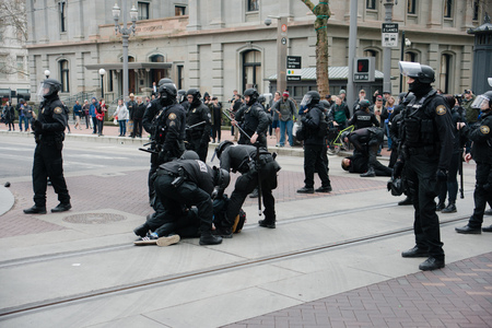 PORTLAND, OREGON JANUARY 25 2017, Police officers in riot gear, arresting people, clearing the roadway of protests of the police reaction to inauguration day protests who were blocking traffic