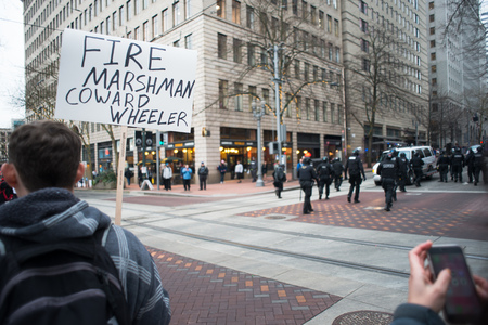 arrests: PORTLAND, OREGON JANUARY 25 2017, Protesters sign reading Fire Marshman, Coward Wheeler,  police walking in the street after clearing it of protesters and making arrests.