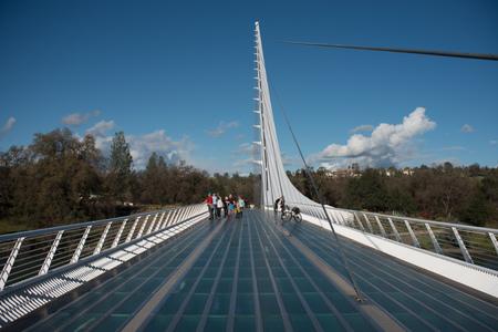 REDDING, CALIFORNIA NOVEMBER 21 2016, People on The Sundial pedestrian bridge over the Sacramento River on a sunny fall day