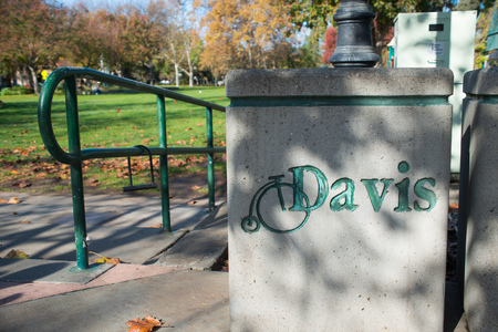 DAVIS CALIFORNIA, NOVEMBER 23 2016, Concrete trash bin with the City of Davis logo on it. In the background, a bike lock attached to a railing.