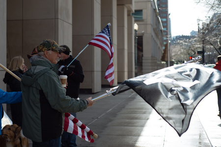 PORTLAND, OREGON MARCH 06 2017, Man in front of the courthouse with a flag protesting the second trial of participants of the occupation of the Malheur Wildlife Refuge and the death of LaVoy Finicum. Editorial