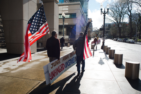 PORTLAND, OREGON MARCH 06 2017, David Fry, acquitted defendant in the first trial of the occupation of the Malheur Wildlife Refuge and others protesting the second trial walking holding american flags Editorial