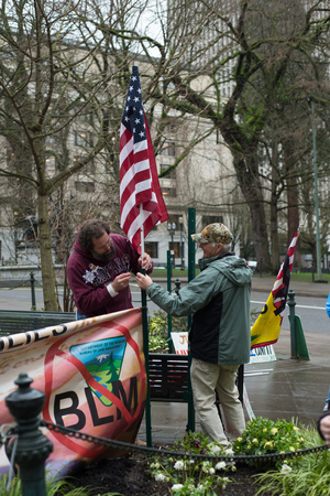 PORTLAND, OREGON MARCH 08 2017, Protesters of the second trial of the occupation of the Malheur Wildlife Refuge attaching an American flag to one of their signs. Stock Photo - 79364366