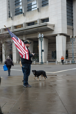 PORTLAND, OREGON MARCH 08 2017, Protester of the second trial of the occupation of the Malheur Wildlife Refuge holding an American flag across from the courthouse.