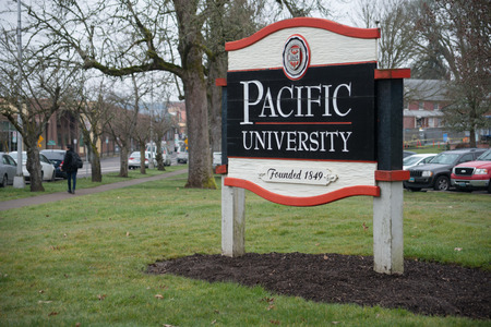 FOREST GROVE, OREGON MARCH 2 2017, A wooden entrance sign for Pacific Univesity, sidewalk and street in the background.