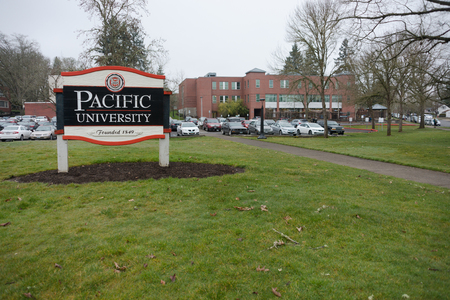 FOREST GROVE, OREGON MARCH 2 2017, A wooden entrance sign for Pacific Univesity, with a school building and parking lot behind it. Editorial