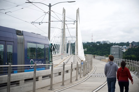 PORTLAND, OREGON, MAY 16 2017, On the Tilikum Crossing bridge with a Streetcar, people walking & jogging across the span.