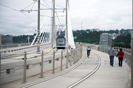 PORTLAND, OREGON, MAY 16 2017, On the Tilikum Crossing bridge with a Streetcar, a bicyclist, and people walking & jogging.