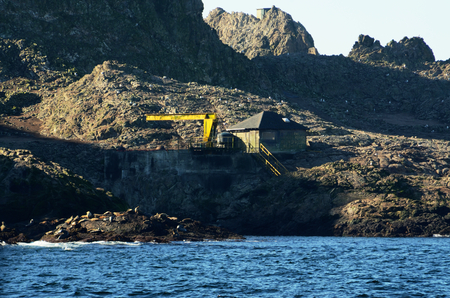 A run-down looking building with Federal Wildlife Refuge No Trespassing No Shooting painted on the side of it and an old crane on the Southeast Farallon Island, outside the San Francisco Bay. Sea Lions are visible on rocks near the water. Editorial