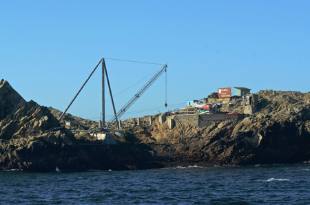 The crane and boat platform on the Southeast Farallon Island, allowing researchers to get on and off the island, and receive supplies. The Farallon National Wildlife refuge sign is visible Stock Photo - 81333010