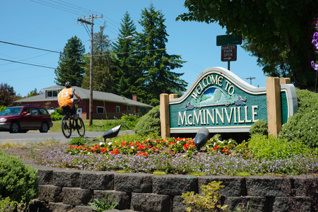 MCMINNVILLE, OREGON JUNE 6TH 2017, A roadside sign welcoming people to the city of McMinnville surrounded by planted flowers. A car and a bicyclist are going by. Editorial