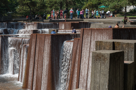PORTLAND, OREGON August 02 2017, Keller Fountain Park on a sunny day, people and kids wading in the  pools of the fountain, and waiting in a long line at a food stand