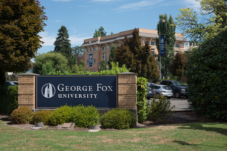 NEWBERG OREGON, AUGUST 15 2017, A sign at an entrance for George Fox University, with a brick building in the background.
