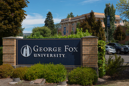 NEWBERG OREGON, AUGUST 15 2017, Close on a sign at an intrance for George Fox University, with a brick building in the background. Editorial