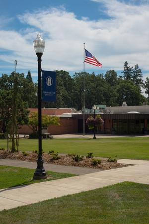 NEWBERG OREGON, AUGUST 15 2017, On the George Fox University campus, a lamp post showing the school logo, and an American Flag waving in front of a school building.