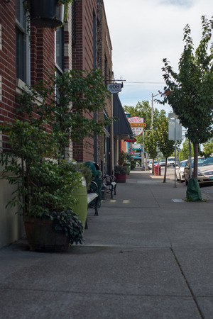 NEWBERG OREGON, AUGUST 15 2017, Looking down a sidewalk in downtown Newberg, benches alongside a brick building. Shops and restaurants visible in the distance. Editorial