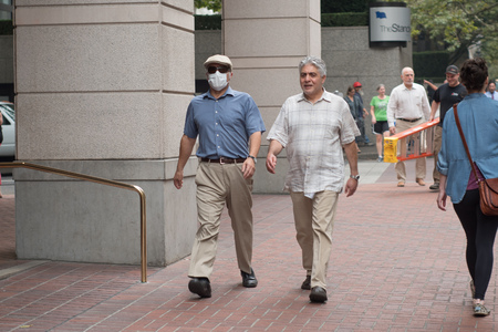 PORTLAND, OREGON SEPTEMBER 09 2017, Men walking on a sidewalk in downtown, one wearing a dust mask to combat breathing in smoke from the wildfires just outside of Portland.