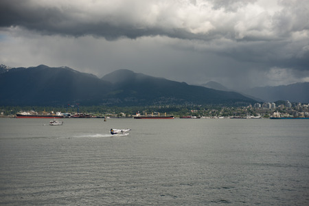 VANCOUVER CANADA JUNE 09 2017, A Seaplane about to take off  in the Burrard Inlet. tanker and cargo ships are in the background, and the mountains, still with snow, are viisable in the distance.