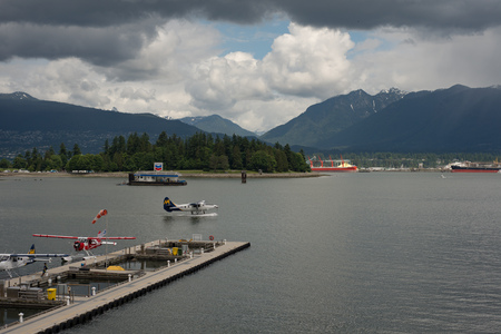 VANCOUVER CANADA JUNE 09 2017, A Seaplane taxis to prep to take off in the Burrard Inlet. Other seaplanes are docked in the foreground, a floating gas station is visible. Editorial