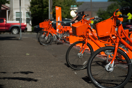 PORTLAND, OREGON JUNE 06 2017, Biketown Bike share program bikes in a rack on a sunny day, traffic and a bicyclist in the background. Stock Photo - 89802745