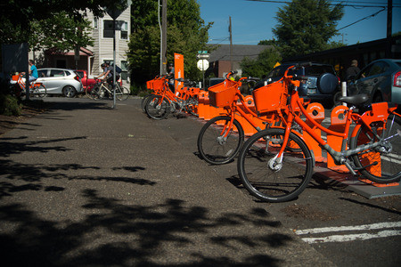 PORTLAND, OREGON JUNE 06 2017, Biketown Bike share program bikes in a rack on a sunny day,  bicyclists and other traffic on the road in the background. Stock Photo - 89802746