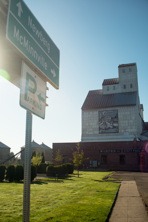 OCTOBER 10 2017, CARLTON, OREGON, The old grainery building in the small town, with a winery below it. In the foreground is a road sign pointing directions to nearby Newberg and McMinnville Editorial