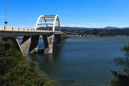 The U.S. Route 101  Alsea Bay Bridge and town of Waldport on the far side of it. A small boat passes underneath the span. Stock Photo