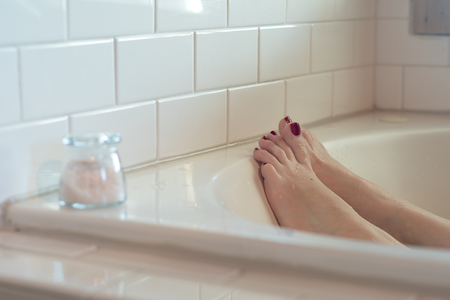 Womens feet with dark purple nail polish in a luxurious bathtub. surrounded by white subway tile.  a small glass container of pink bath salts rests at the edge.