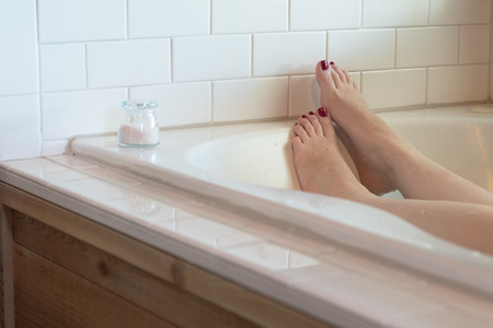 Womens feet with dark purple nail polish in a luxurious bathtub surrounded by white subway tile, with wood along the side. a small glass container of pink bath salts rests at the edge.