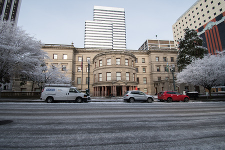 PORTLAND, OREGON, FEBRUARY 21 2018: City Hall in the winter with a fine dusting of snow on it, trees covered. The road in covered in ice. Editorial