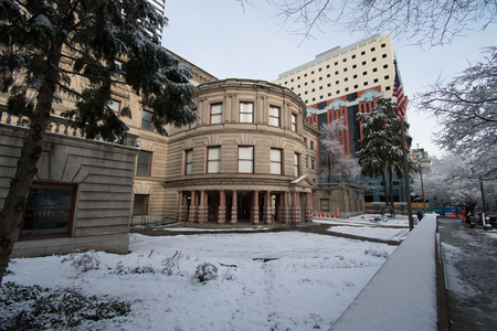 PORTLAND, OREGON, FEBRUARY 21 2018: City Hall in the winter with a fine dusting of snow on it, trees covered. A path shoveled clear for people to enter. Editorial