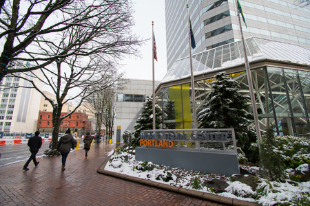 PORTLAND, OREGON, FEBRUARY 21 2018: People walking past a World Trade Center building in Portland on a winter morning with snow on the ground.