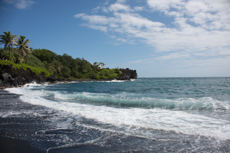On the Waianapanapa Black Sand Beach on the island of Maui, Hawaii on a sunny day. Stock Photo