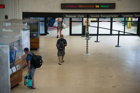 KAHULUI, HAWAII, FEBRUARY 26 2017: A sign above exit doors at the main Airport on the island of Maui. People walking out.