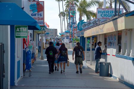 NEWPORT BEACH, CALIFORNIA, JUNE 10 2017 Shops, food vendors and rides along a walkway with tourists walking up and down. Editorial
