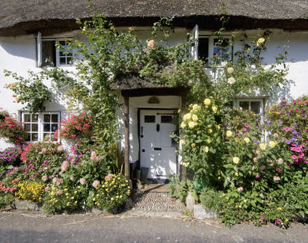 thatched cottage with flowers doorway white village Stock Photo - 614685