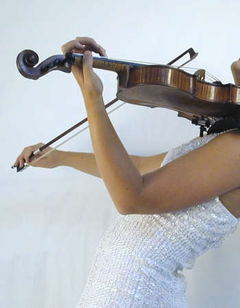 girl playing violin in evening dress on stage at concert photo