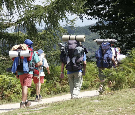 walkers with backpacks and rucksacks walking along mountain footpath