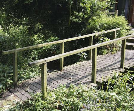 bridging the gap: wooden footbridge across stream in cottage garden Stock Photo