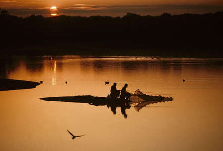 warwickshire: fishermen  fishing on lake with sunset behind earlswood lakes warwickshire midlands england uk