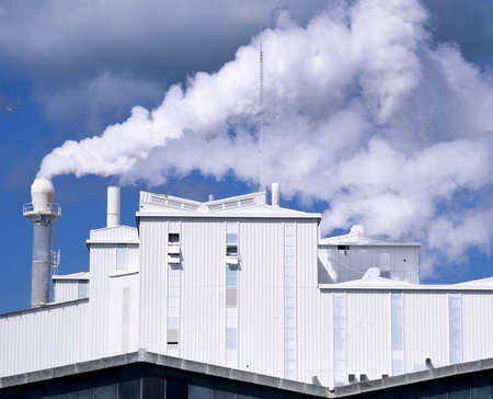 windy energy: factory with white smoke coming out of chimney Stock Photo