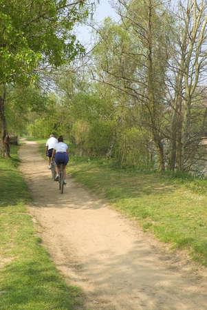cardiovascular exercising: couple cycling along path alongside river worcester uk