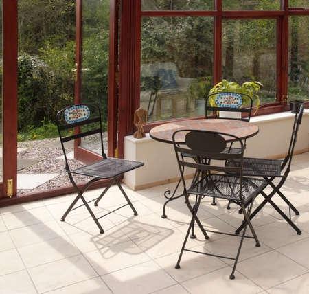 wintergarten: Conservatory legt Stuhlbetriebsraum im Haus nahe bei Garten ver Lizenzfreie Bilder