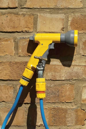 hosepipe: yellow blue plastic hosepipe and tap in garden