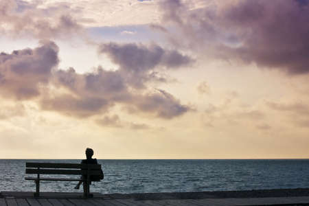 looking out: woman sitting on bench looking out to sea sunset sky
