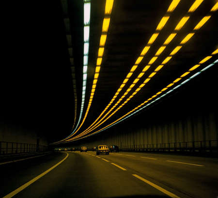overtake: cars on road in tunnel with lights overhead Stock Photo