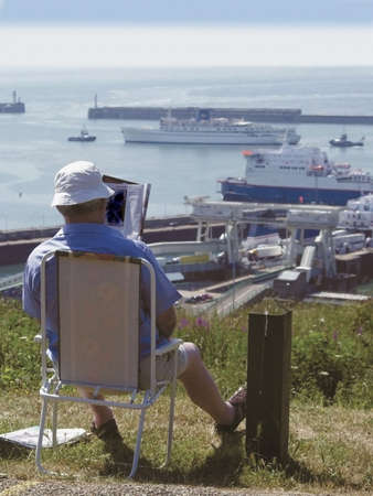 kent dover docks man sitting in chair reading newspaper  photo