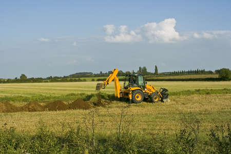 unsightly: digger in countryside digging holes in the ground