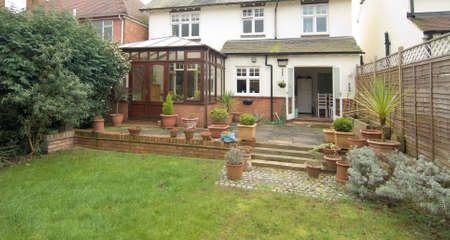 conservatory: conservatory on back of detached house with garden and lawn