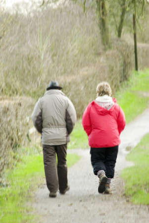 two middle aged walkers on footpath walking back to car photo